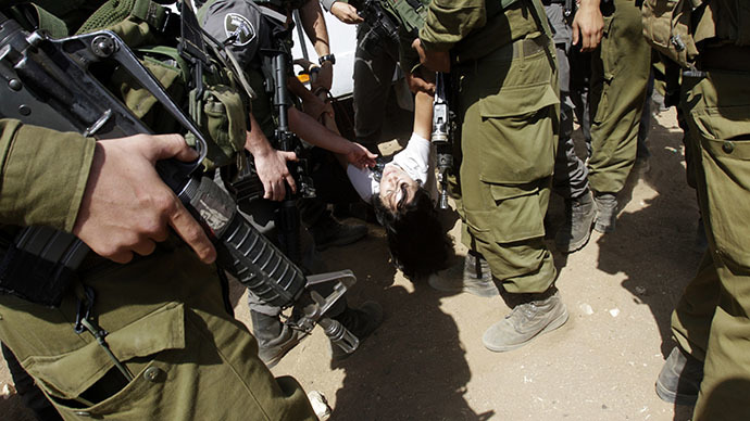 Israeli soldiers carry French diplomat Marion Castaing after removing her from her truck containing emergency aid, in the West Bank herding community of Khirbet al-Makhul, in the Jordan Valley September 20, 2013. (Reuters / Abed Omar Qusini)
