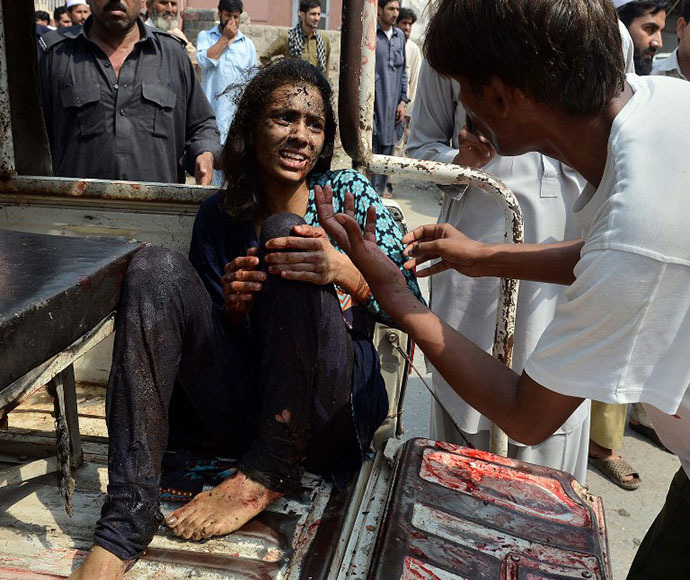 A Pakistani man helps an injured Christian woman on her arrival at the hospital after two suicide bomb attacks on a Church in Peshawar on September 22, 2013. (AFP Photo / A. Majeed)