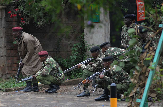 Armed Kenyan policemen take cover outside theWestgate mall in Nairobi, on September 23, 2013. (AFP Photo / Simon Maina)