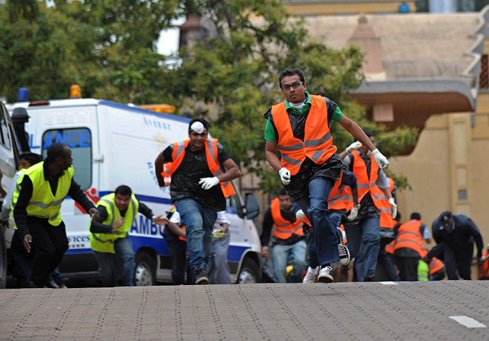 Volunteers from the asian-community run for cover on September 23, 2013, after hearing a volley of gunshots at the scene of a siegeof an upmarket shopping mall by al-shebab, Somalia based al-Qaeda linked terror network. (AFP Photo / Tony Karumba)