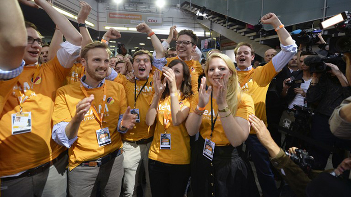 Supporters of the Christian Democratic Union (CDU) celebrate as exit polls are broadcast on television in Berlin on September 22, 2013, after the German general elections. (AFP Photo / Odd Andersen)