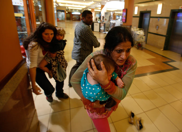 Women carrying children run for safety as armed police hunt gunmen who went on a shooting spree in Westgate shopping centre in Nairobi September 21, 2013 (Reuters / Goran Tomasevic)