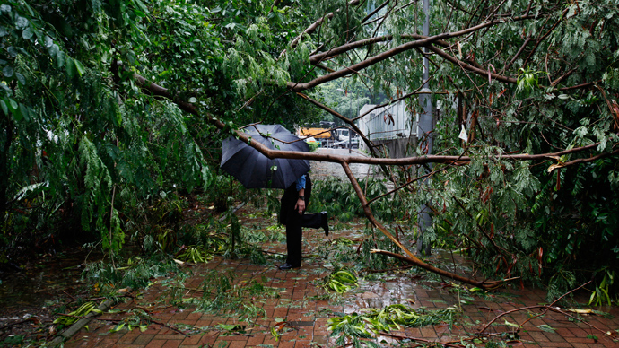 A man walks under fallen branches on a pavement at a residential district after Typhoon Usagi hit Hong Kong September 23, 2013 (Reuters / Bobby Yip)
