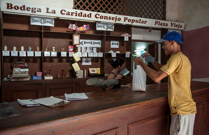 "A customer gets his monthly rice quota in a store where people can use their ""libreta"", a ration card which since 1963 has allowed Cubans to buy basic food supplies at cheap -- and heavily subsidized -- prices, in Havana (AFP Photo)"