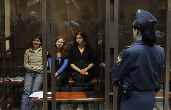 "Members of the female punk band ""Pussy Riot"" (L-R) Yekaterina Samutsevich, Maria Alyokhina and Nadezhda Tolokonnikova sit in a glass-walled cage before a court hearing in Moscow October 10, 2012. (Reuters/Maxim Shemetov)"