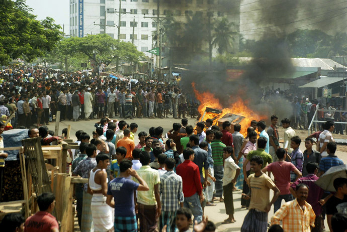 Garment workers set fire in a bench as they block a street during a protest in Gazipur September 23, 2013. (Reuters)