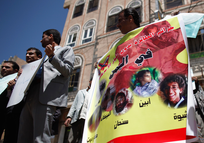 An activist holds a banner with photos of people killed in drone attacks, during a protest against the U.S. drone strikes in Yemen outside the U.S. embassy in Sanaa April 29, 2013 (Reuters / Khaled Abdullah)