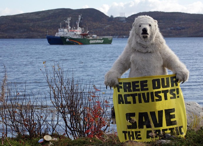 Greenpeace activist dressed as a polar bear holding a banner in front of the Arctic Sunrise Greenpeace's Arctic protest ship in Kola Bay at the military base Severomorsk on the Kola peninsula on September 24, 2013 (AFP Photo / Greenpeace / Igor Podgorny)