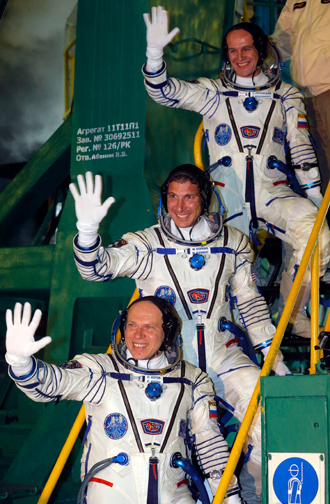 US astronaut Michael Hopkins (C) and Russian cosmonauts Oleg Kotov (L) and Sergey Ryazanskiy (R), crew members of the mission to the International Space Station (ISS), wave on September 26, 2013 before the launch of Soyuz-FG rocket at the Russian-leased Baikonur cosmodrome in Kazakhstan (AFP Photo / Pool)