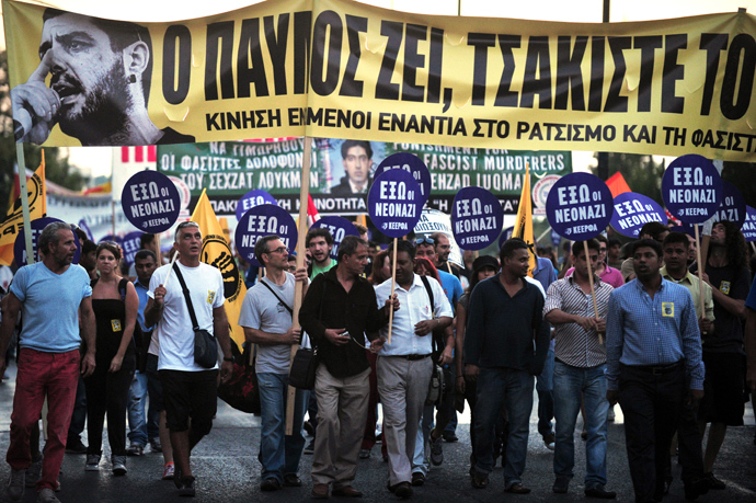 "Protesters hold on September 25, 2013 a banner featuring a picture of the murdered anti-fascist musician, 34-year-old musician Pavlos Fyssas, and reading: ""Pavlos lives, crack the fascists"", during a massive demonstration in Athens heading toward the offices of the neo-Nazi party Golden Dawn (AFP Photo)"