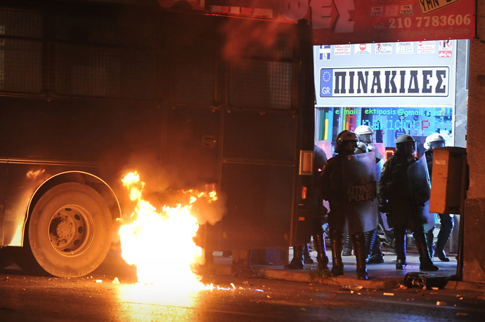 A molotov cocktail burns next to a riot police van on September 25, 2013 at the end of massive demonstration against the fatal September 18 stabbing of 34-year-old musician Pavlos Fyssas by unemployed truck driver George Roupakias (AFP Photo)