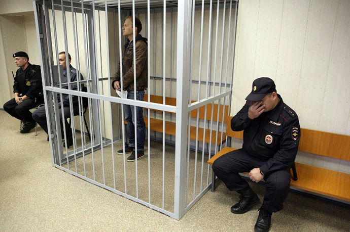 A handout picture taken late on September 26, 2013, and provided by Greenpeace International shows Greenpeace International contracted freelance photographer Denis Sinyakov sitting in a defendant cage in a court in the northern Russian city of Murmansk. (AFP Photo / Igor Podgorny)