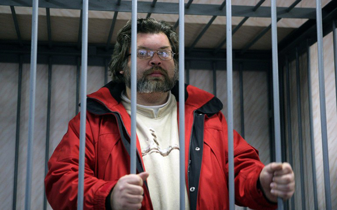 A handout picture taken late on September 26, 2013, and provided by Greenpeace International shows Greenpeace International expert Roman Dolgov standing in a defendant cage in a court in the northern Russian city of Murmansk. (AFP Photo / Igor Podgorny)