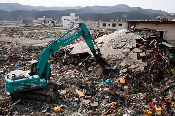 Japanese workers use a hydraulic machine to demolish a wrecked building in the tsunami-devastated town of Rikuzentakata, Iwate prefecture, on April 2, 2011 (AFP Photo / Yasuyoshi Chiba)