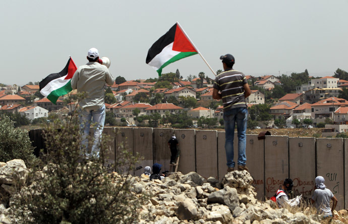 Palestinian protesters wave the national flag as their comrades climb Israel's controversial separation barrier during clashes with Israeli security forces following a demonstration against Israeli settlements and its separation wall, in the West Bank village of Nilin near the Jewish settlement of Hashmonaim (background), on May 31, 2013. (AFP Photo)