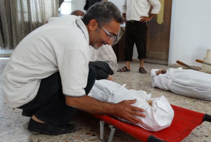 A handout image released by the Syrian opposition's Shaam News Network on August 23, 2013, shows a relative weaping over the boody of one of his family members killed during what Syrian rebels claim to be a toxic gas attack by pro-government forces in eastern Ghouta earlier in the week, during their funeral on the outskirts of Damascus. (AFP/Shaam News Network)