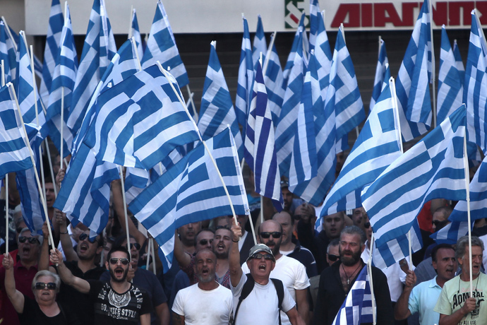 Supporters of the extreme far-right Golden Dawn party hold Greek flags and shout slogans during a protest in solidarity of the arrested lawmakers in front of the police headquarters of Greek Police, in Athens, on September 28, 2013 (AFP Photo / Angelos Tzortzinis)