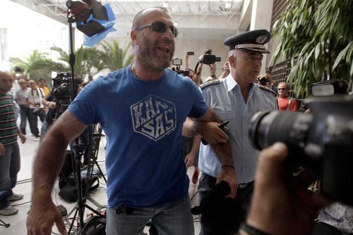 Lawmaker of extreme-right Golden Dawn party Nikolaos Mihos (L) is escorted by a police officer as he arrives at the Greek police headquarters in Athens September 28, 2013 (Reuters / John Kolesidis)
