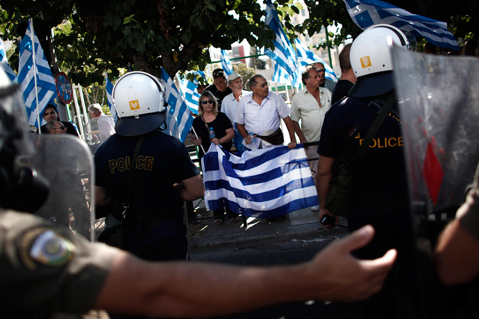 Supporters of the extreme far-right Golden Dawn party hold Greek flags as riot police tries to move them away during a protest in solidarity of the arrested lawmakers in front of the police headquarters in Athens on September 28, 2013 (AFP Photo / Angelos Tzortzinis)