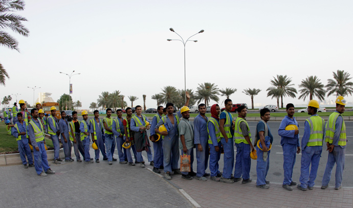 Foreign workers wait for their bus at a construction site in Doha, Qatar (Reuters / Fadi Al-Assaad)