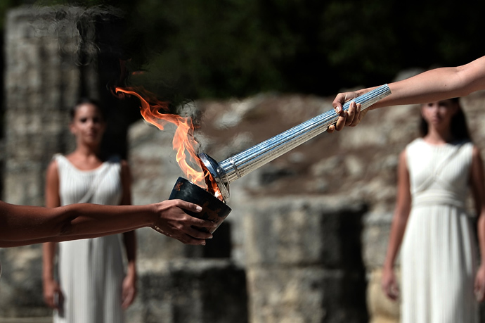 Greek actress Ino Menegaki (R) acting as the high priestess holds the Olympic Flame at the Temple of Hera on September 29, 2013 during the lighting ceremony in ancient Olympia (AFP Photo / Aris Messinis)