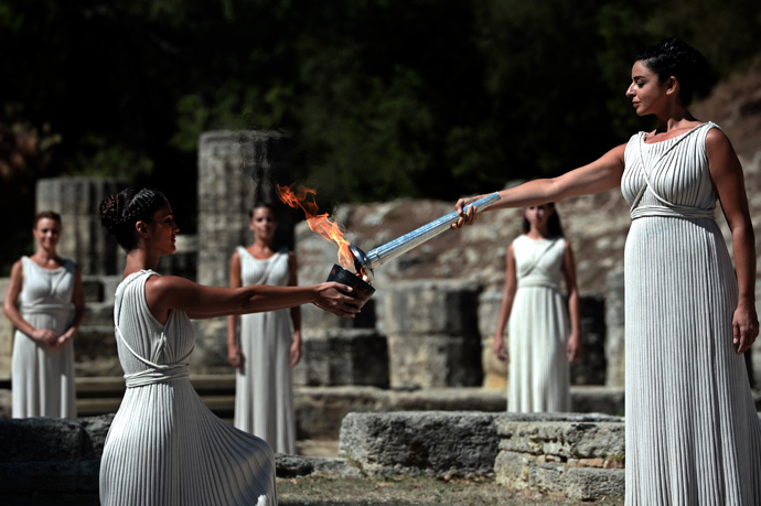 Greek actress Ino Menegaki acting as the high priestess passes the Olympic Flame at the Temple of Hera on September 29, 2013 during the lighting ceremony in ancient Olympia (AFP Photo / Aris Messinis)