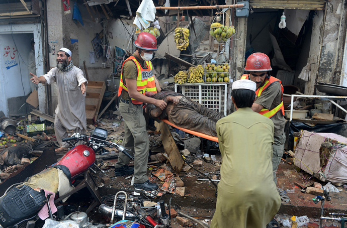 Pakistani volunteers carry a blast victim at the site of a bomb explosion in the busy Kissa Khwani market in Peshawar on September 29, 2013 (AFP Photo / A. Majeed)