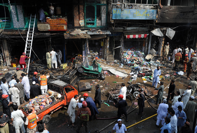 Pakistani security officials and volunteers gather at the site of a bomb explosion in the busy Kissa Khwani market in Peshawar on September 29, 2013 (AFP Photo / A. Majeed)