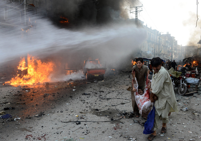 Pakistani men carry an injured blast victim at the site of a bomb explosion in the busy Kissa Khwani market in Peshawar on September 29, 2013 (AFP Photo / Hasham Ahmed)