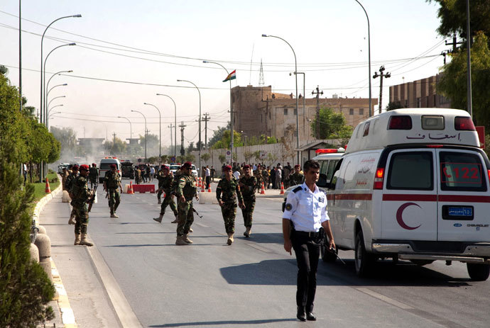 Iraqi Kurdish security forces and medical services are seen at the site of an explosion in Arbil, outside the headquarters of the Kurdish aayesh security services in the capital of Iraq's autonomous Kurdistan region, on September 29, 2013. (AFP Photo / Safin Hamed)