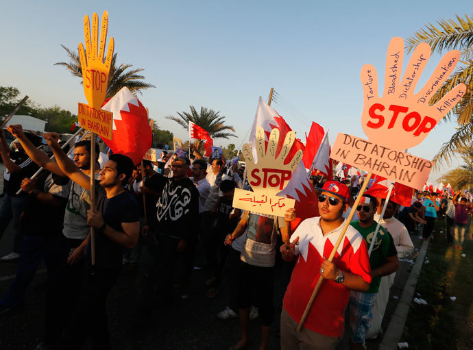 "Anti-government protesters holding banners saying ""Stop Dictatorship In Bahrain"" as they participate in a rally called by Bahrain's main opposition Al Wefaq in Budaiya, west of Manama, September 27, 2013.(Reuters / Hamad I Mohammed)"