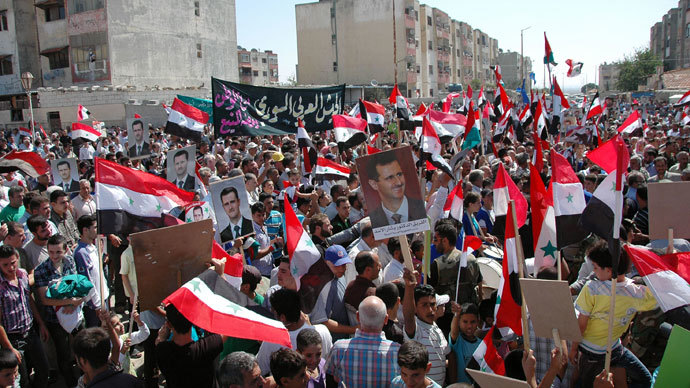 Syrian demonstrators waving their national flag and pictures of President Bashar al-Assad during a march near the central city of Homs, in support of the country's army.(AFP Photo / SANA)