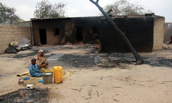 Children sit in front of a burnt house in the remote northeast town of Baga on April 21, 2013 after two days of clashes between officers of the Joint Task Force and members of the Islamist sect Boko Haram on April 19 in the town near Lake Chad, 200 kms north of Maiduguri, in Borno State. (AFP Photo)
