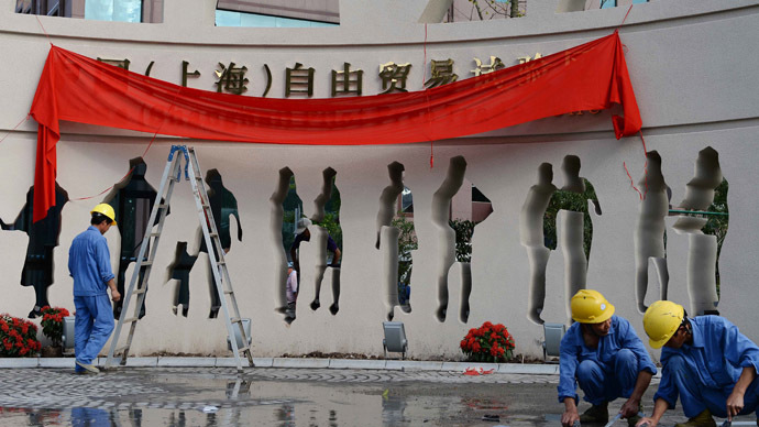 "This picture taken on September 23, 2013 shows workers decorating a gate of Shanghai Waigaoqiao Free Trade Zone (FTZ) with signage reading ""China (Shanghai) Pilot Free Trade Zone"" before its formal launch on September 29. (AFP Photo/China Out)"