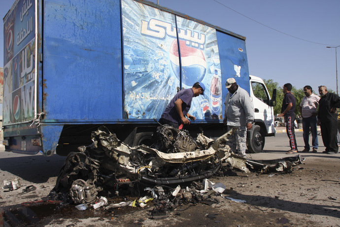 Residents inspect the mangled remains of a vehicle at the site of a car bomb attack in Baghdad's Sadr City, September 30, 2013. (Reuters/Wissm al-Okili)
