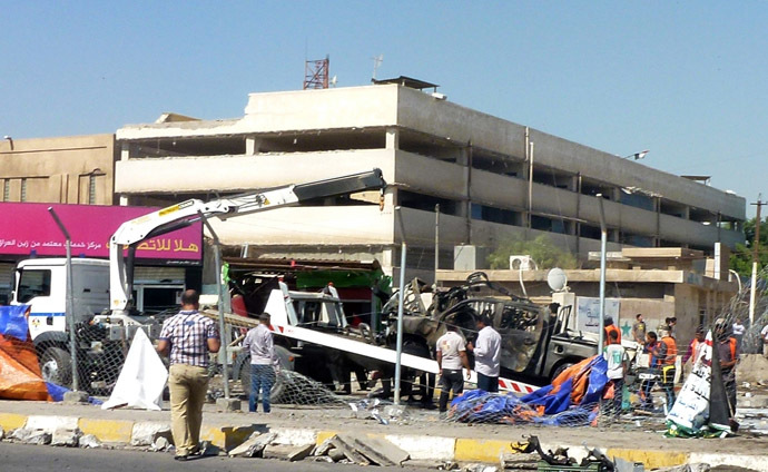 A destroyed vehicle is removed following a car bomb in a car park in Baghdad Jadida, on September 30, 2013. (AFP Photo)