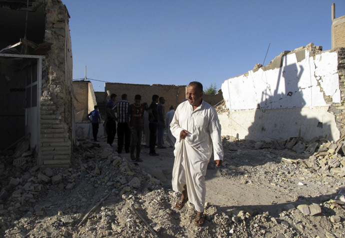 A man walks near a damaged Shi'ite mosque a day after a suicide bomb attack in Hilla, 60 km (40 miles) south of Baghdad, September 30, 2013. (Reuters/Habib)