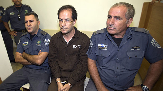 Ali Mansouri, 58, arrested at Ben Gurion Airport on suspicion of espionage, sits in between guards at the Petah Tikva District Court on the first day of their trial on September 30, 2013. (AFP Photo / Jack Guez)