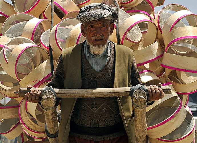 An elderly Afghan man pulls a handcart loaded with hand-made sieves (AFP Photo / Shah Marai)