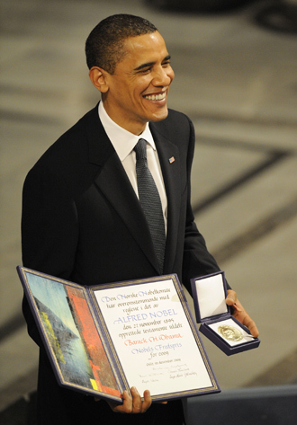 Nobel Peace Prize laureate, US President Barack Obama poses on the podium with his diploma and gold medal during the Nobel ceremony at the City Hall in Oslo on December 10, 2009 (AFP Photo / Olivier Morin)