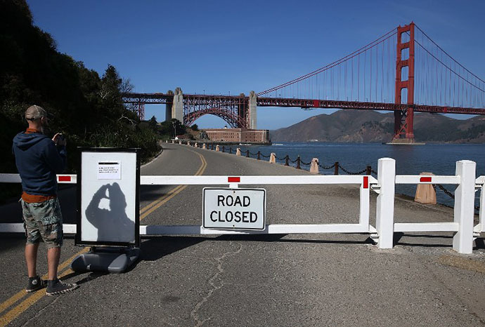 A visitor takes a picture of a sign announcing the closure of the Fort Point National Historic Site due to the partial government shutdown on October 1, 2013 in San Francisco, California. (AFP Photo / Justin Sullivan)