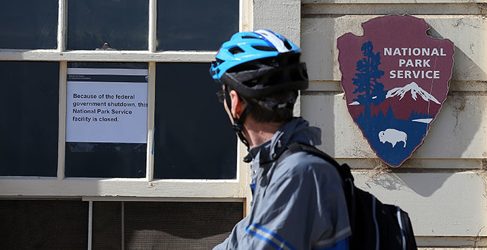 A cyclist reads a sign announcing the closure of a Park Service facility at Crissy Field due to the partial government shutdown on October 1, 2013 in San Francisco, California. (AFP Photo / Justin Sullivan)