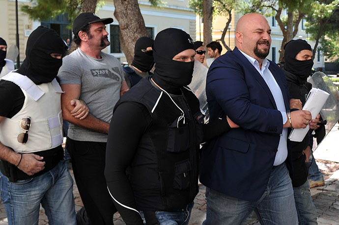 Policemen bring Golden Dawn lawmakers Ilias Panagiotaros (2nd R) and Giannis Lagos (2nd L) to the court in Athens on October 1, 2013. (AFP Photo / Louisa Gouliamaki)