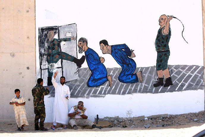 Libyans are pictured in front of a mural painting depicting a torture scene outside Tripoli's Abu Slim jail, scene of a 1996 massacre of prisoners, during a three-day exhibition in the gutted grey complex on June 29, 2012. (AFP Photo / Mahmud Turkia)