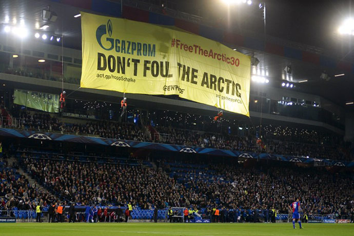 Greenpeace activists (top) hold a demonstration during the UEFA Champions League group E football match between Switzerland's Basel and Schalke of Germany on October 1, 2013 at the St. Jakob-Park Stadium in Basel. (AFP Photo / Fabrice Coffrini)