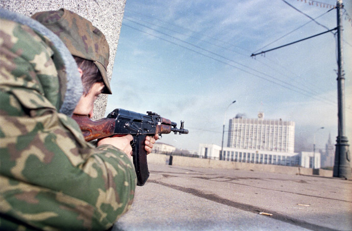 A picture taken on October 4, 1993, shows a pro-Yeltsin forces officer firing his Kalashnikov assault rifle at the Russian parliament building, also known as the White House, during the parliamentary revolt in Moscow. (AFP Photo/Alexander Nemenov)