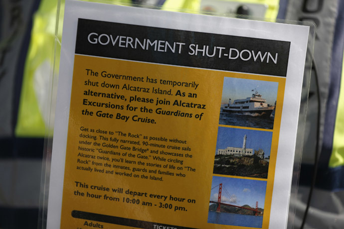 Security officer Jarvis Landlum holds a sign informing people on the government shutdown of Alcatraz Island, a tourist attraction operated by the National Park Service, in San Francisco, California October 1, 2013. (Reuters/Stephen Lam)