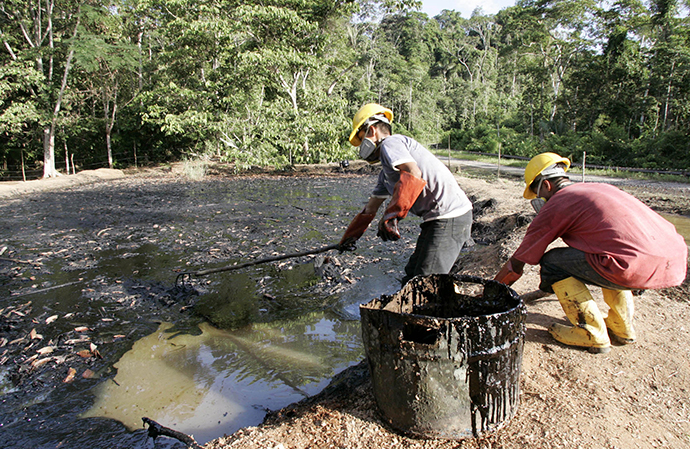 Oil workers clean up a contaminated pool in Taracoa December 10, 2007. (Reuters / Guillermo Granja)