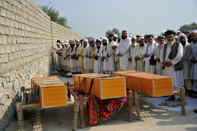 Afghan men pray alongside the coffins of civilians, allegedly killed in a NATO air strike, on the outskirts of Jalalabad in Nangarhar province on October 5, 2013. (AFP Photo / Noorullah Shirzada)