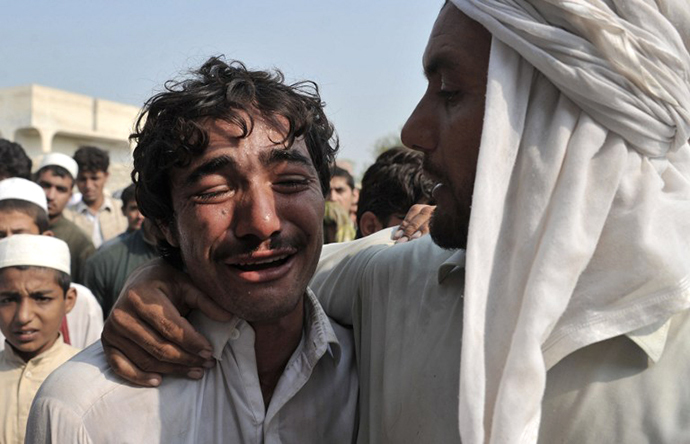 An Afghan man weeps over the death of his brother, allegedly killed in a NATO air strike, on the outskirts of Jalalabad in Nangarhar province on October 5, 2013. (AFP Photo / Noorullah Shirzada)